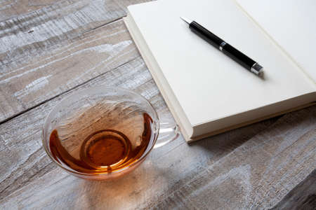 small group of objects: Read tea, blank book and pen Stock Photo