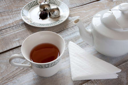 infuser: Red tea, teapot and tea ball infuser on table