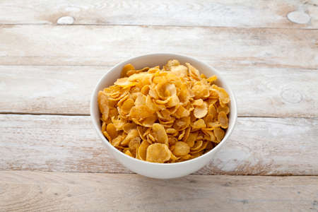 cornflakes: Bowl of cornflakes on rustic background
