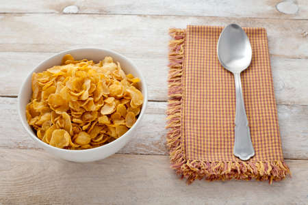 cornflakes: Bowl of cornflakes, spoon and napkin on rustic background