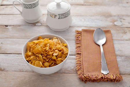 cornflakes: Bowl of cornflakes, spoon, sugar bowl on rustic background Stock Photo