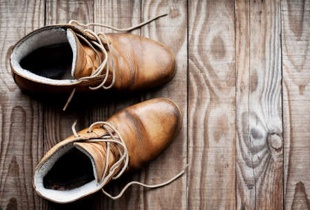 muddy clothes: Pair of old boots view from above on rustic wooden background