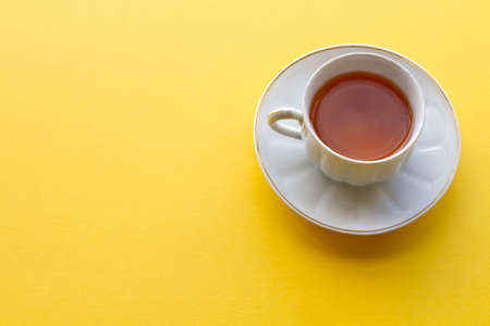red tea: Cup of red tea on yellow background