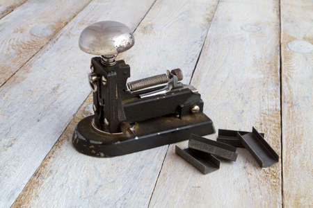 staplers: Old metal stapler and staples on tustico background