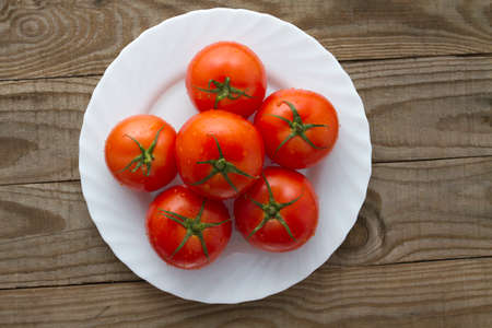 medium group of objects: Vine tomatoes on a white plate Stock Photo