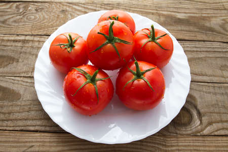 medium group: Vine tomatoes on a white plate Stock Photo