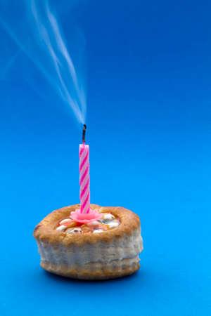 unlit: Smoke unlit candle on cake and blue background Stock Photo