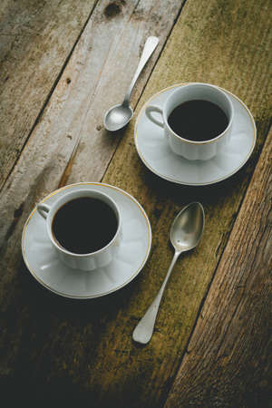 medium group of objects: Black coffee in porcelain cup on rustic table