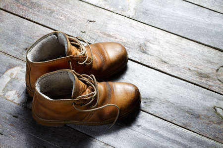 shoelace: Old boots on rustic wooden floor Stock Photo