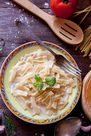 Close up of Carbonara noodles with mint leaves on rustic table and kitchen cutlery 스톡 콘텐츠