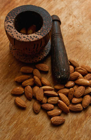 ponder: Almond nuts on a wooden desk and a ponder Stock Photo