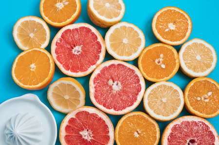 nutricion: Juicy oranges, lemons and grapefruits and a squeezer on a table