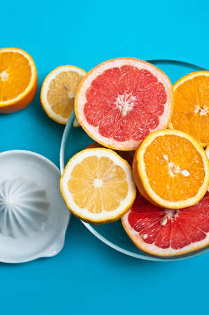nutricion: Citruses in a glass bowl on the blue background with a squeezer