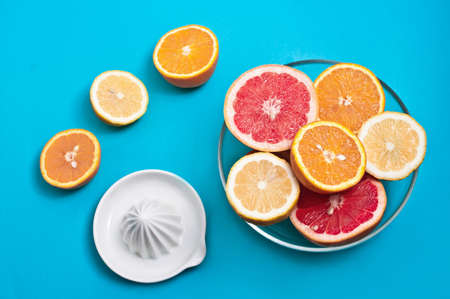 nutricion: Oranges lemons and pink grapefruits in a bowl and a squeezer on a blue background Stock Photo