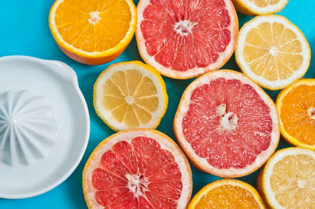 nutricion: Juicy oranges, lemons and grapefruits with a squeezer on the blue background