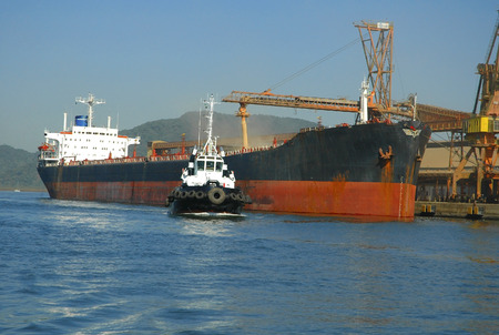 barge: Large grain ship docked at Port of Santos harbour and tugboat in action.