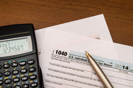 tax forms: 1040 Tax Return Form with calculator on wodden background Stock Photo
