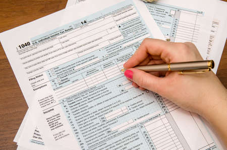 tax forms: Woman hand filling income tax forms 1040