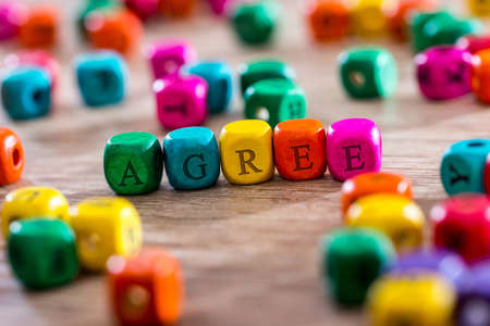 agree - word created with colored wooden cubes on desk.