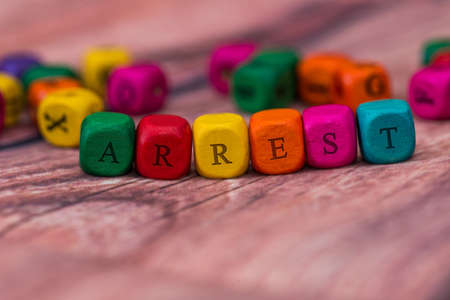 arrest - word created with colored wooden cubes on desk.