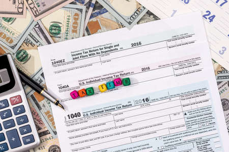 tax form with money, wooden cubes, pen, calendar and calculator.