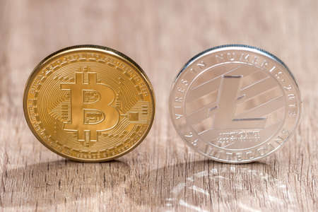 Bitcoin and litecoin standing together on wooden background