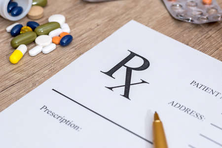 Medical prescription and drugs and pen on table