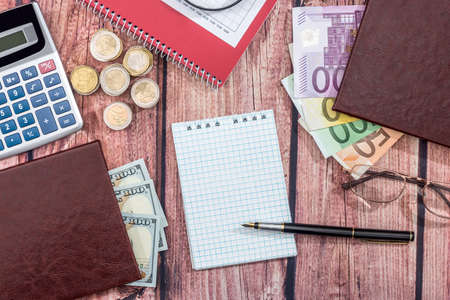euro vs dollar with notepad, coin, pen on desk
