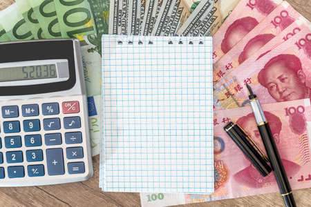 100 dollar, euro and yuan bills with notepad and calculator and pen on desk.