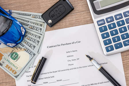 documant, dollar, pen, calculator and toy car with keys.
