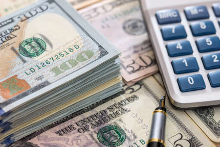us dollar with pen and calculator close up.