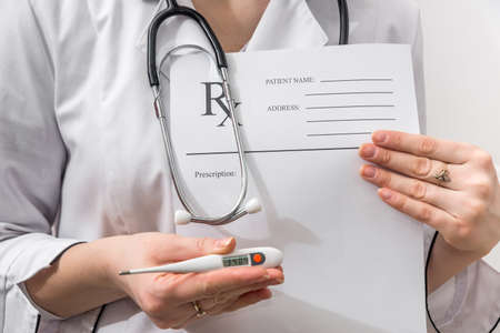 female doctor holding rx paper in hand