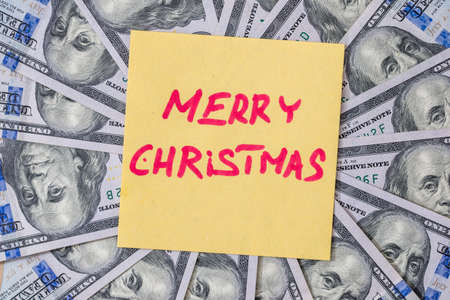 Merry Christmas text on a background of dollars