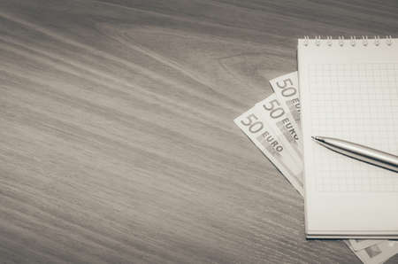 empty notepad with euro banknote, pen on table