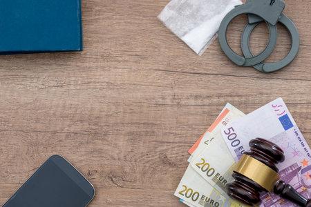 handcuff, ueros, drug and phone on desk.