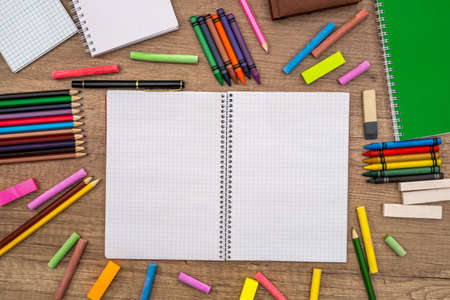 empty notepad with color chalks and pencils on desk.