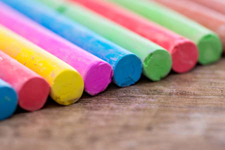 Pile of colored chalk closeup as background. Selective focus.