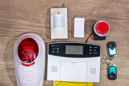 alarm system home on wooden desk.
