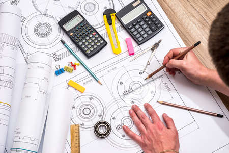 Mechanical engineer with work at technical drawings and work tools