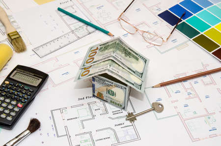 dollar banknotes as model house on a construction plan for house building 写真素材