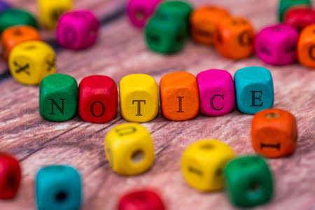 notice - word created with colored wooden cubes on desk.