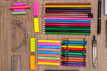 School Supplies - colored chalks and pencils on a wooden background. Archivio Fotografico
