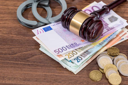 handcuffs with law hammer and euro bills, coin on desk. business concept. Stock Photo