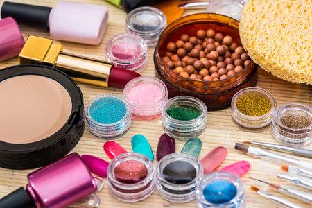 different makeup products - lipstick, eye shadows, nail polish, powder
