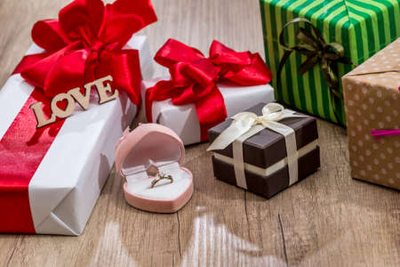Many decorated gift boxes with ribbon bows and open box with gold ring