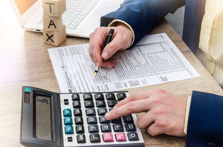 Man counting on calculator and filing 1040 form