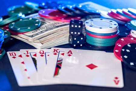Black background with poker chips, cards, dollars and bones