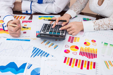 Financial analysts team counting business reports with calculator