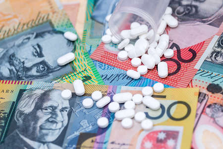Dispersed white tablets on australian dollar banknotes