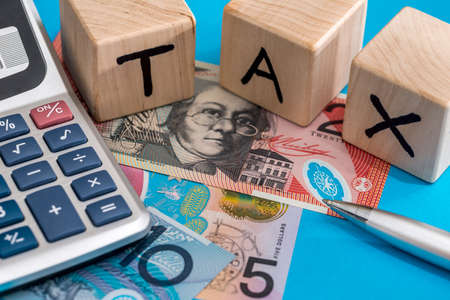 text tax with australian dollar, pen and calculator